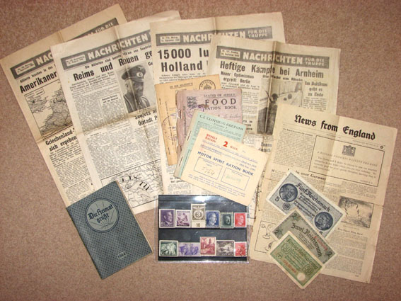 A selection of papers including news papers, leaflets, ration books, stamps, money and an army diary.